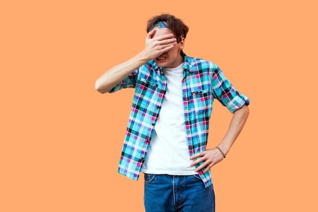 これは見たくない。カジュアルな青い市松模様のシャツのヘッドバンドが立って、目を覆っていて見たくないショックを受けた若い男の肖像画。オレンジ色の背景に分離された屋内スタジオショット