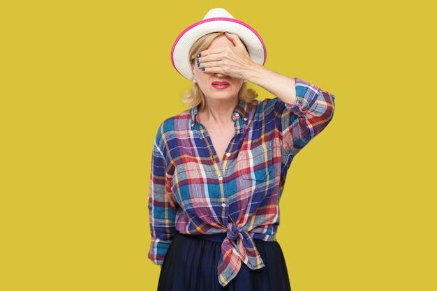 見たくない。立って、手で目を閉じた白い帽子のカジュアルなスタイルの怖いまたはショックを受けたモダンでスタイリッシュな成熟した女性の肖像画。黄色の背景に分離された屋内スタジオショット。
