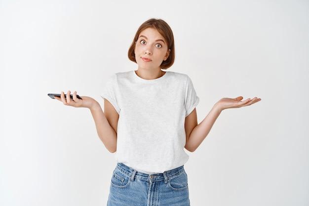 Я не знаю. невежественная европейская женщина пожимает плечами, понятия не имеет, держит мобильный телефон и смотрит вопрос, стоя у белой стены