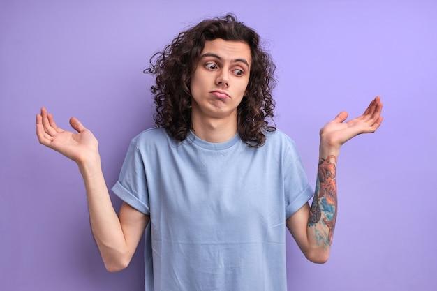 私は腕を上げて立っている青いカジュアルなtシャツで混乱したハンサムな若い男性の肖像画を知りません...