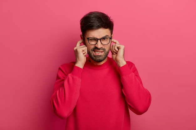 I dont want to listen it! annoyed unshaven man winks eye, hears loud noise, avoids unpleasant sound, wears glasses and red jumper, doesnt hear somebodys advice, closes ears with index fingers