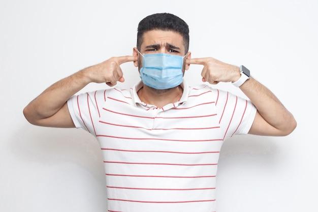 코로나바이러스에 대해 듣고 싶지 않습니다. 수술용 의료 마스크를 쓰고 카메라를 보고 귀에 손가락을 대고 있는 슬픈 혼란스러운 남자의 초상화. 실내 샷, 흰색 배경에 고립입니다.