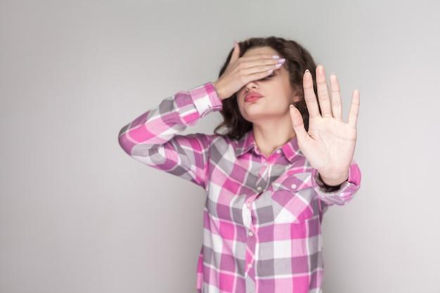 見たくない。ピンクの市松模様のシャツを着た混乱した少女が立って恐れ、手で目を閉じてブロックしようとしました。灰色の背景に分離された屋内スタジオショット。