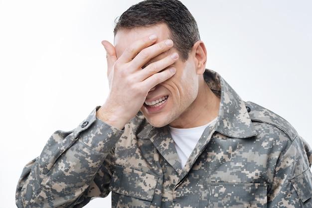 나는 그것을보고 싶지 않다. 군복을 입고 문제를 생각하면서 눈을 가리는 불행한 쾌활한 잘 생긴 남자