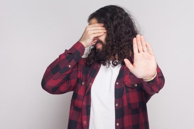 私はこれを見たくありません。目を覆って立っている市松模様の赤いシャツのひげと黒の長い巻き毛を持つハンサムな男の肖像画とジェスチャーを停止します。灰色の背景に分離された屋内スタジオショット。