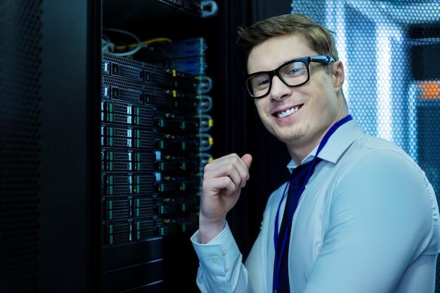 Я счастлив. вдохновленный красивый оператор улыбается и стоит у оборудования