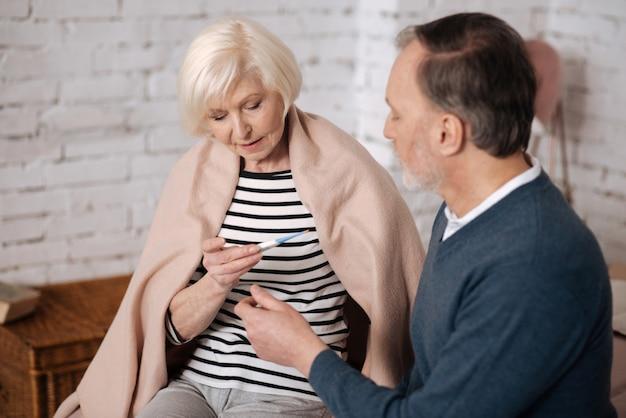 Я заболела гриппом. довольно старая женщина смотрит на термометр, сидя накрытой одеялом рядом со своим мужем.