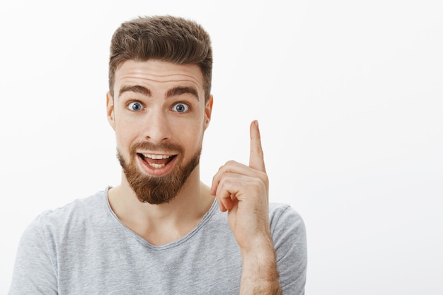 I got and idea. enthusiastic and excited happy creative caucasian guy with beard and cute blue eyes raising index finger in eureka gesture talking with boss presenting perfect plan over gray wall