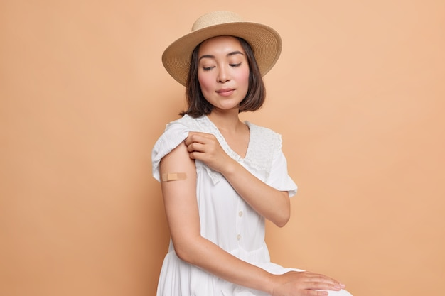 I got my coronavirus vaccine. serious asian lady looks attentively on place of inoculation wears aid band