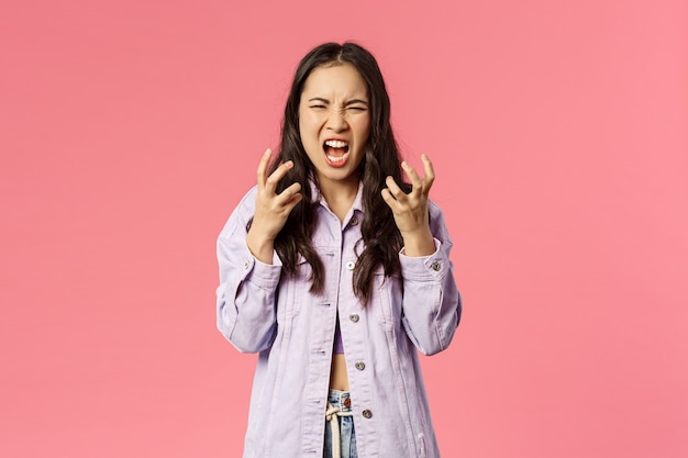Я всех вас ненавижу. портрет возмущенной, раздраженной и сердитой молодой девушки, корейской девушки-подростка, кричащей в ярости, гримасничающей и сжимающей руки в кулаки от гнева, выходящего из себя, розовый фон