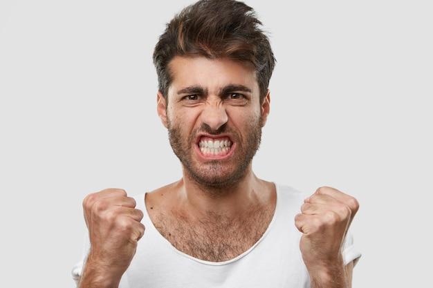 Odio l'idea! immagine ravvicinata di uomo con la barba lunga infastidito con acconciatura alla moda, stringe i denti, alza i pugni, perde la pazienza