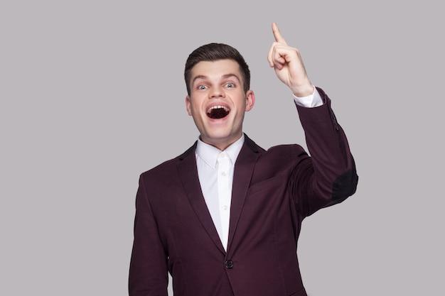 У меня есть хорошая идея. портрет счастливого довольного красивого молодого человека в фиолетовом костюме и белой рубашке, стоящего, смотрящего на камеру с удивленным лицом. крытая студия выстрел, изолированные на сером фоне.