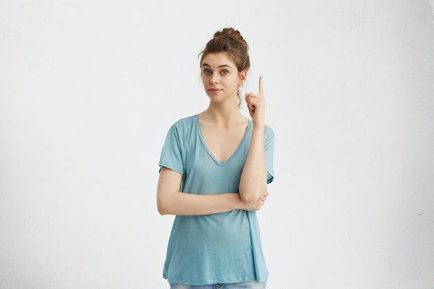 좋은 생각이 있어요! 손가락을 위쪽으로 향하게 유지하는 머리 롤빵을 가진 똑똑한 재치있는 예쁜 소녀. 검지 손가락으로 제스처를 만드는 그녀의 머리 위에 뭔가 보여주는 귀여운 젊은 백인 여자
