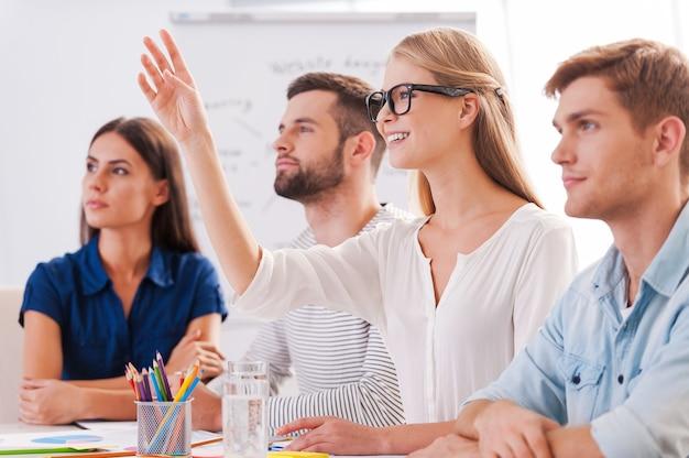 質問があります!テーブルに一緒に座って、美しい女性が手を上げて笑っている間、スマートカジュアルウェアのビジネスマンのグループ