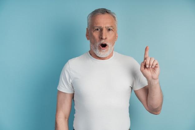 나는 아이디어가 있습니다. 노인은 검지 손가락을 들어 올리는 몸짓을하고 있습니다. 좋은 아이디어가 있습니다.
