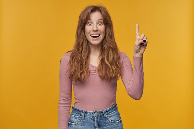 У меня есть мысль. молодая рыжая самка с веснушками и волнистыми волосами указывает пальцем вверх на желтом