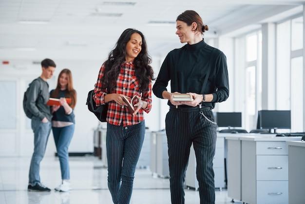 좋은 계획이 있습니다. 휴식 시간에 사무실에서 걷는 젊은 사람들의 그룹입니다.