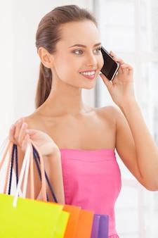 たくさん売りに出しています。ショッピングバッグを持って携帯電話で話しているピンクのドレスの美しい若い女性