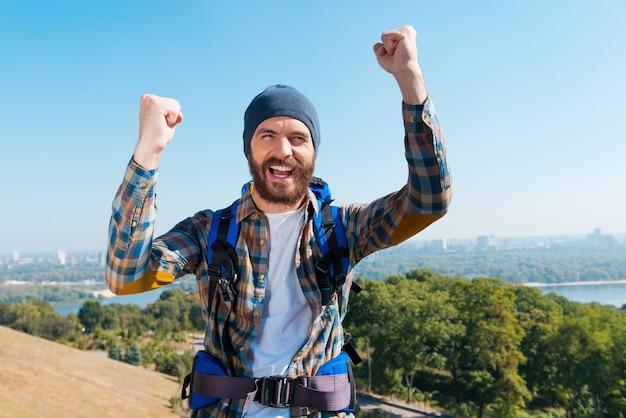 Я сделал это! счастливый молодой человек, несущий рюкзак и смотрящий в камеру с поднятыми руками