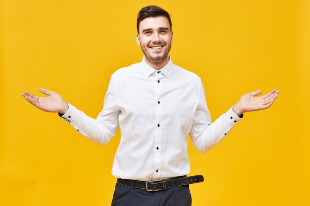 I have no idea.  emotional attractive young unshaven man smiling happily, spreading arms wide, making welcoming gesture, showing presentation, advertising product at copyspace wall