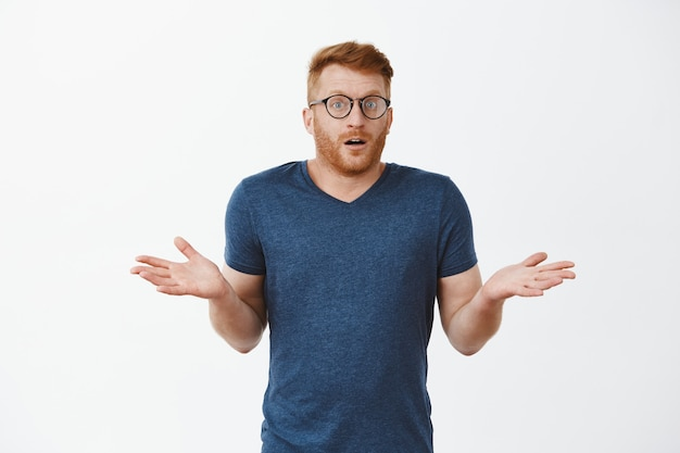 I have no idea how that happened. portrait of clueless cute masculine male with red hair in glasses and t-shirt, shrugging with spread palms and gazing confused and uncertain over grey wall