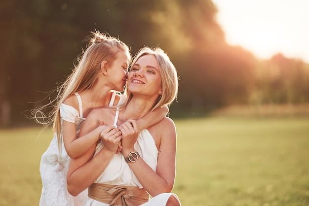 У меня для тебя есть секрет. мать и дочь наслаждаются выходными вместе, гуляя на открытом воздухе в поле. прекрасная природа.