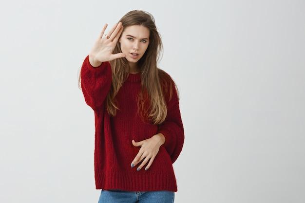 Ho i punti di forza per fermarti. lo studio ha sparato della ragazza messa a fuoco attraente in maglione rosso sciolto che tira i palmi verso la macchina fotografica nella fermata o nel gesto sufficiente, essendo serio e sicuro.