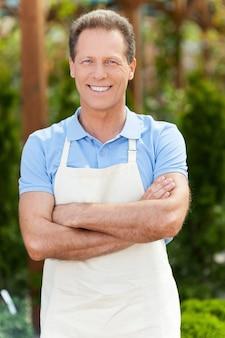 나는 세상에서 가장 좋은 직업을 가지고 있다! 온실에 서 있는 동안 팔짱을 끼고 웃고 있는 앞치마를 입은 잘생긴 성숙한 남자