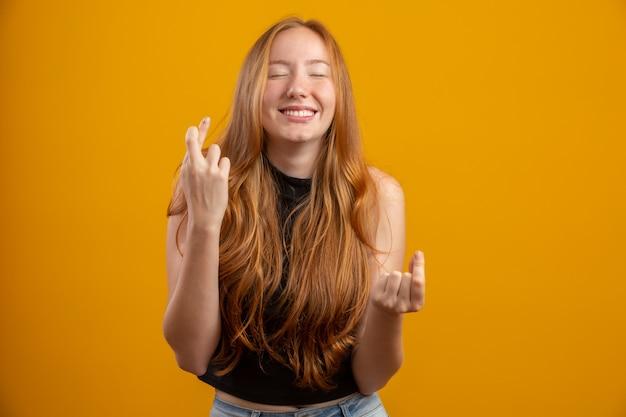 Я должен победить. радостная молодая рыжая сука сжимает зубы, поднимает пальцы, делает желаемое желание, вьющиеся волосы, смешанная раса, кавказская девушка, ждет хороших новостей, стоит над желтой стеной.