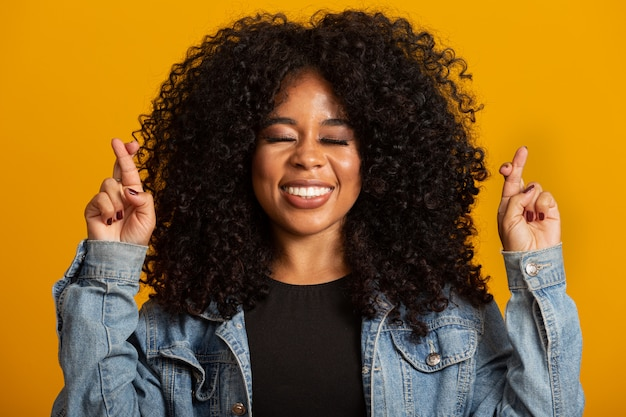 I have to win. joyful young brunette female clenches teeth, raises fingers crossed, makes desirable wish, curly hair, mixed race, african, brazilian girl, waits for good news, stands over yellow wall