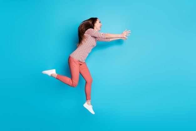 Я давно тебя не видел. фото сбоку в полный рост веселая сумасшедшая девушка прыгать бегать copyspace держаться за руки хочу обнять приветствовать добро пожаловать друг в белых штанах изолированный синий цвет фона