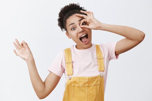 Ho zero soldi ma non mi preoccupo. affascinante ragazza africana felice con i capelli ricci in tuta gialla, che mostra il gesto giusto o giusto sopra gli occhi e sorride con gioia, divertendosi nella cerchia familiare