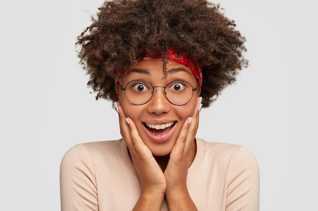 나는 이것을 상상할 수 없다! 아름답고 놀랍고 행복한 어두운 피부를 가진 여성은 광범위하게 미소를 짓고, 뺨을 만지고, 재미있는 표정을 가지고 있으며, 광학 안경을 쓰고, 흰 벽 위에 고립 된 아프로 헤어 스타일을 가지고 있습니다.