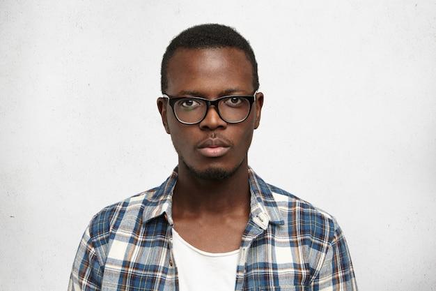 私は何が欲しいか正確に知っています。彼の将来の計画とキャリアに自信を持っている、真剣で穏やかな表情を持つスタイリッシュなメガネの魅力的な若いアフリカ系アメリカ人学生のヘッドショット