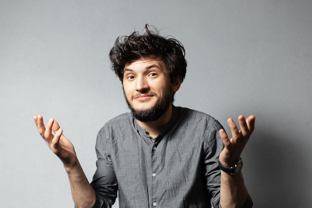 I don't know. portrait of bearded young guy with disheveled hair, showing helpless gesture with hands. isolated on grey.