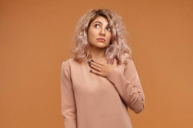Non lo so. ritratto di confuso bug emotivo eyed giovane femmina caucasica tenendo la mano sul petto e alzando lo sguardo con espressione facciale indecisa incapace, perso per le parole