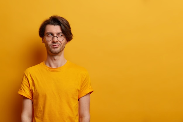 I know what i need. devious mysterious adult man looks with sly expression aside, has evil intention, nice idea or scheme, poses against yellow wall, empty space