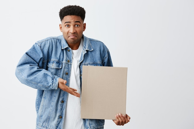 I don't know what is this. young unhappy black-skinned man with afro hairstyle in white t shirt and denim jacket holding paper bard in hand, pointing at it with curious and confused face expression