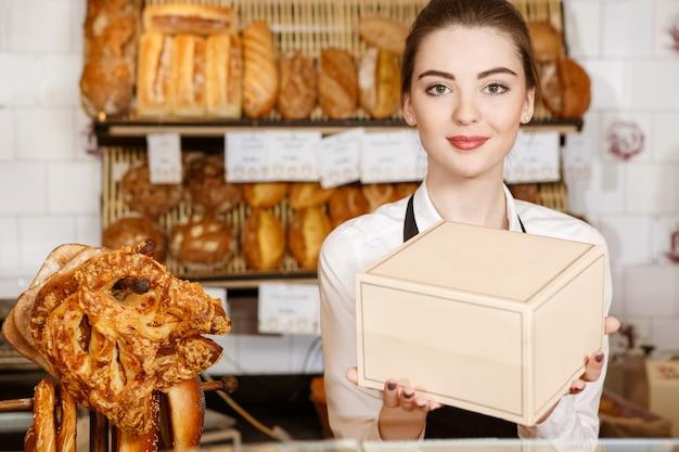 Я знаю, что нравится моим клиентам. красивая улыбающаяся женщина-пекарь, протягивая коробку с десертами из пекарни