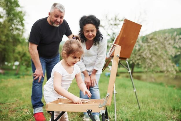 私は何をすべきか知っています。祖母と祖父は孫娘と屋外で楽しんでいます。絵画の構想