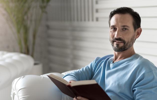 Я люблю книги. хорошо выглядящий привлекательный умный мужчина читает книгу и улыбается, отдыхая на диване