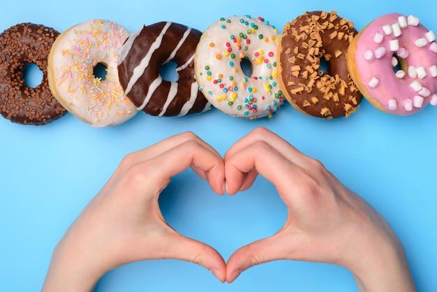 私は不健康なジャンクフードの概念を食べるのが好きです。頭上の上の上部は、青い背景の上に分離された手で心を示す人の手の拡大写真