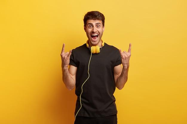 ヘビーメタルが好き!うれしそうな若い男性は狂っていて、両手でホーンジェスチャーをし、ヘッドフォンで好きな音楽を聴きます