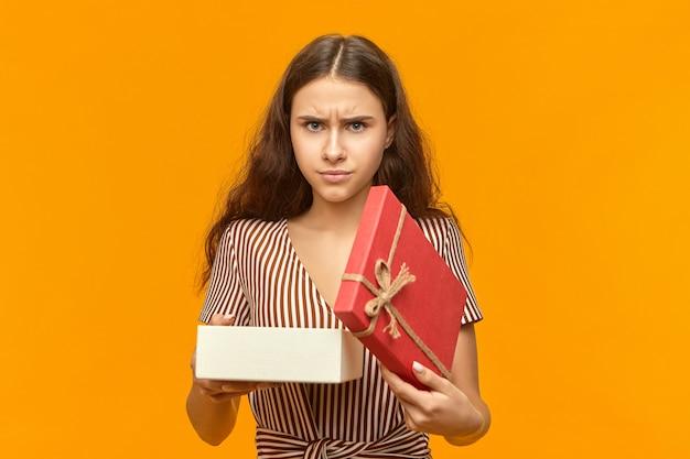 Non mi piace colpo isolato della giovane donna alla moda scontenta con la scatola di apertura dei capelli ondulati