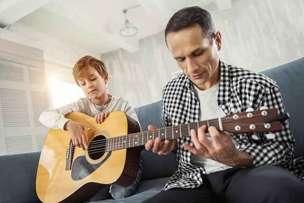 遊ぶことが好き。ギターを持っている魅力的な集中した小さな金髪と彼の父親は彼にギターを弾くように教え、彼らはソファに座っています