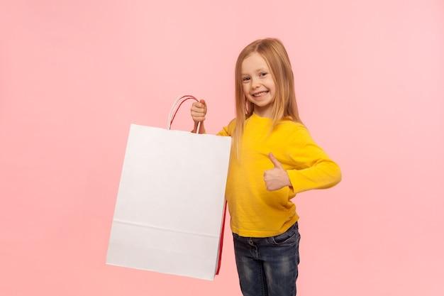 나는 어린이 가게에서 쇼핑하는 것을 좋아합니다. 큰 패키지를 들고 엄지손가락을 치켜들고 쇼핑 판매에 만족하는 평온한 행복한 어린 소녀의 초상화. 분홍색 배경에 고립 된 실내 스튜디오 촬영