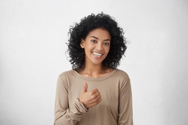 私はすきです。よくやった。幸せな若い暗い肌の女性がカジュアルな長袖tシャツを着て親指を立て、元気に笑って、誰かへの彼女のサポートと敬意を示しています。ボディランゲージ