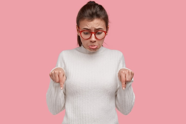 Non mi piace questo. la donna disperata fa il broncio e aggrotta le sopracciglia per la delusione e il rimpianto, indica al piano, ha momenti difficili, vede qualcosa di spiacevole