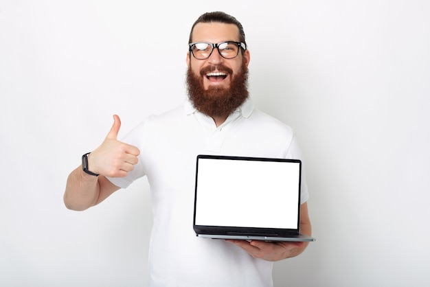 I like this offer. bearded man is holding thumb up and an open laptop.