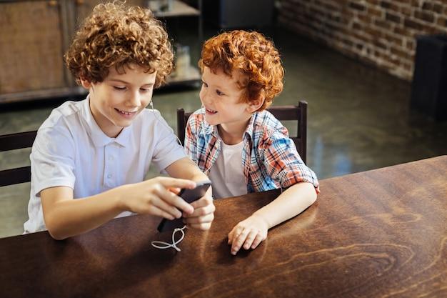 난이게 좋아. 흥분된 생강 머리 소년이 넓게 웃고 이어폰을 끼고 음악을 즐기면서 형과 이야기하는 것에 선택적 초점을 맞 춥니 다.
